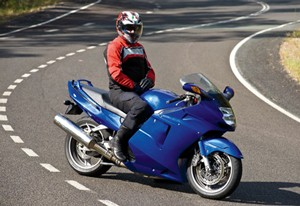 Photo of a person in a safety outfit and helmet, sitting on a motorbike