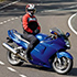 Photo of a rider straddling a blue motorcycle